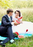 The bride and groom eating watermelon Royalty Free Stock Photo