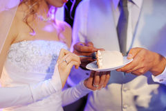 A bride and a groom are eating a wedding cake Royalty Free Stock Photography