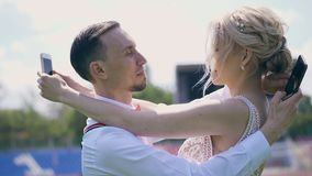 The bride and groom embrace each other and simultaneously look at mobile phones, use social networks. The concept of. Internet addiction, dependence on the stock footage