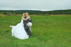 Bride and groom embrace on field Stock Photos