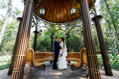 Bride and groom embrace and look at each other in the arbour. Couple in love at wedding day in the park Royalty Free Stock Photography