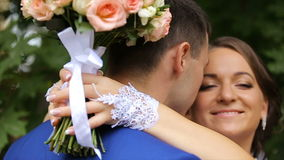 Bride and groom in an embrace in the park. Beautiful young bride and groom embracing in the park on a summer day.Wedding concept. Happy Newlywed woman and man in stock video footage