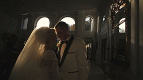 Bride and groom embraces in palace on sunset stock video footage