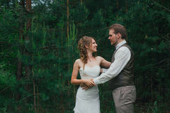Bride and groom are embracing against the background forest Stock Image