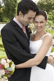 Bride And Groom Embracing In Garden Stock Image