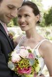 Bride And Groom Embracing In Garden Stock Photos