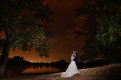 Bride and groom embracing by the lake under the stars. Royalty Free Stock Photos