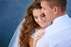 Bride and groom embracing at the lake for a walk Stock Photo