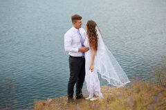 Bride and groom embracing at the lake for a walk Royalty Free Stock Photo