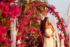 Bride and groom embracing near arch of flowers in Maldives Royalty Free Stock Photography