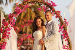 Bride and groom embracing near arch of flowers in Maldives Royalty Free Stock Images
