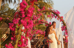 Bride and groom embracing near arch of flowers in Maldives Stock Photo