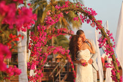 Bride and groom embracing near arch of flowers in Maldives Stock Image