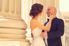 Bride and groom embracing near columns Royalty Free Stock Photo