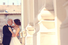 Bride and groom embracing near columns Royalty Free Stock Photography