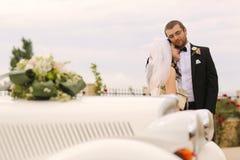 Bride and groom embracing near retro car Stock Photography