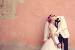 Bride and groom embracing near wall Royalty Free Stock Images