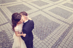 Bride and groom embracing on paved street Royalty Free Stock Photography