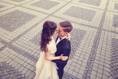 Bride and groom embracing on paved street Stock Photos