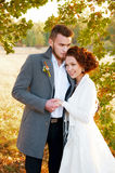 Bride and groom embracing. Romantic autumn outdoor setting. Royalty Free Stock Images
