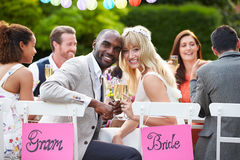Bride And Groom Enjoying Meal At Wedding Reception. Looking To Camera Smiling Royalty Free Stock Photos