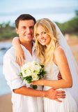 Bride and groom, enjoying time together in a beach Royalty Free Stock Photography