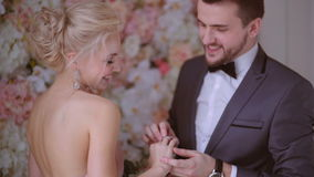 Bride and groom. The bride and groom exchange rings at a wedding ceremony in the studio on a background of beautiful flowers. Wedding in style pale pink stock footage