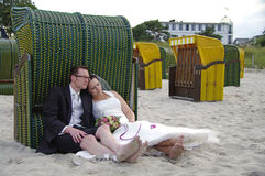 Bride and groom exhausted at the beach stock photography