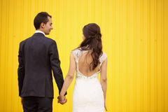 Bride and groom facing yellow wall Royalty Free Stock Photo