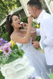 Bride and groom feeding cake stock photos