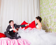 Bride and groom fighting with pillows in bed Stock Photo