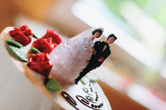 Bride and groom figurine. On top of a wedding cake - selective focus Stock Images