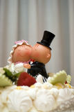 Bride and groom figurines. Comical bride and groom figurines on top of wedding cake Royalty Free Stock Photo