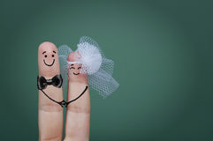 Bride and groom fingers. Two happy fingers decorated as bride and groom with veil and bow tie Royalty Free Stock Images