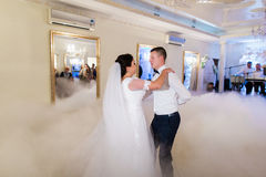 Bride and groom first wedding dance in white bright hall with fogged dancefloor.  Royalty Free Stock Image