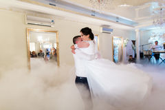 Bride and groom first wedding dance in white bright restaurant hall with fogged dancefloor.  Stock Photo