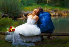 Bride and groom fishing together - romantic wedding concept. Stock Photo