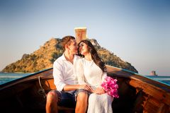 Bride and groom float in longtail boat. Brunette bride in white wedding dress and handsome groom float in longtail boat to island at sunrise stock images