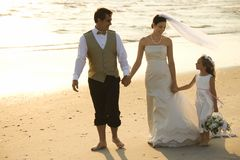 Bride, groom and flower girl. Caucasian mid-adult bride, mid-adult groom and flower girl holding hands walking barefoot on beach royalty free stock photography
