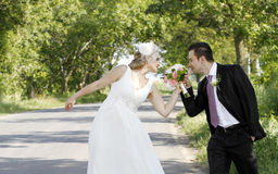 Bride and groom with flowers. A newlywed bride and groom smelling flower bouquet while standing on a tree-lined country road royalty free stock photos