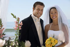 Bride And Groom With Flowers At Beach Royalty Free Stock Image