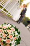 Bride and groom with flowers in front Stock Photography
