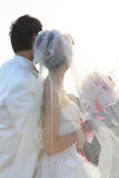 Bride and groom with flowers in hand Stock Photo