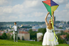 Bride and groom flying a kite on a wedding day. Bride and groom flying a kite together on a wedding day royalty free stock photo