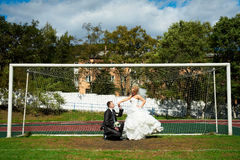 Bride and groom on the football field. In the gate Royalty Free Stock Image