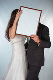 Bride and groom with a frame for photos Royalty Free Stock Photo