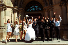 Bride, groom and friends jump in the front of a big door of the Stock Photography