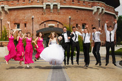 Bride, groom and friends jump standing in the front of an old fo Royalty Free Stock Photo