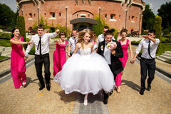 Bride, groom and friends jump standing in the front of an old fo Stock Images