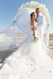 Bride and groom in front of arch. Bride and groom at the carpet in front of the arch of flowers Stock Photography